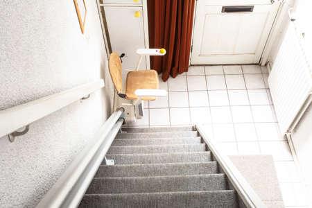 Automatyczna winda schodowa na klatce schodowej zabierająca osoby starsze i niepełnosprawne w górę i w dół po domu