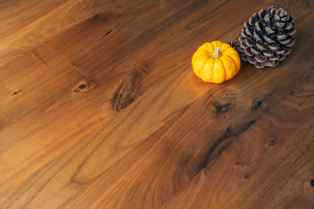 Orange, yellow pumpkin with pine cone on a brown wooden table, Autumn composition top view, copy space. space for text season nature concept Stock Photo