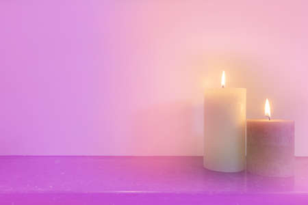 Two burning candles in front of purple pink background, light pastel colors modern design, space for text background