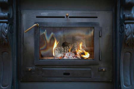 Primo piano tradizionale della stufa a legna nera con fiamme di fuoco, interni accoglienti dal design antico