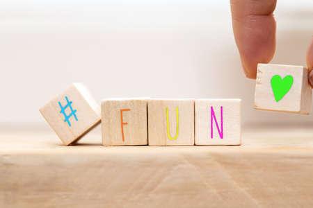 Cubos de madera con hashtag y la palabra diversión en varios colores, primer plano de fondo del concepto de redes sociales Foto de archivo