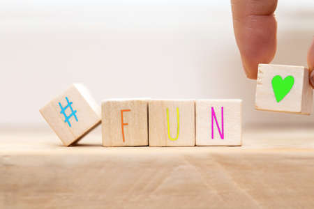 Wooden cubes with hashtag and the word Fun in various colors, social media concept background close-up Stock Photo