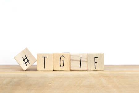 Cubi di legno con Hashtag e la parola tgif, che significa grazie a Dio è venerdì, primo piano sullo sfondo del concetto di social media