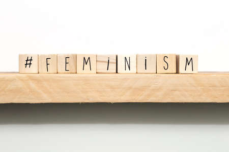 Wooden cubes with a hashtag and the word Feminism near white background, social media concept