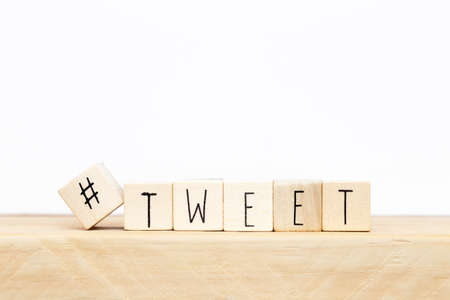 Wooden cubes with a hashtag and the word Tweet, social media concept near white background
