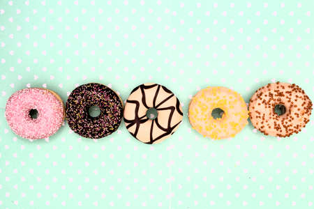 various colored delicious donuts on white background, space for text