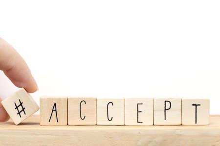 Cubes en bois avec un hashtag et le mot Accepter, concept de médias sociaux près du gros plan de fond blanc