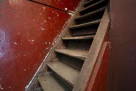 Old damaged brown wooden stairs and red wall leading to the attic, needs renovation