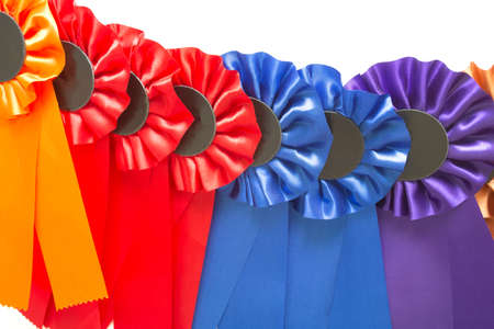 A lots of ribbons rosettes medals overlapping in a row background, horse riding throphys various colors