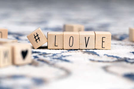 Wooden cubes with a hashtag and the word Love, social media and valentines concept background beauty