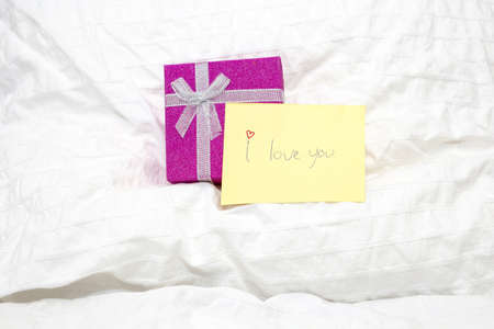 closeup of a little yellow note with handwritten i love you on white sheets of the bed and a giftbox, valentines concept
