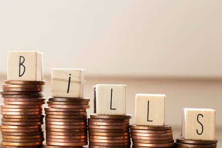 Wooden blocks with the word bills and pile of coins, money climbing stairs Payment of taxes and of debt to the state. Concept of financial crisis and problems. Risk management. Debt exemption. loan