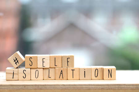 Wooden cubes with the word Self isolation and a question mark for Covid-19, coronavirus needs quarantine concept. Stock Photo