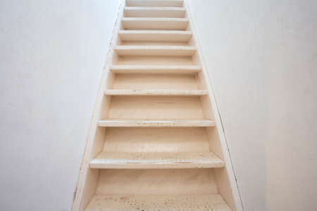 Basic white wooden stairs with white wall modern design, needs renovation close-up