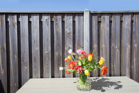 Bright springtime bunch of colorful flowers in a glass vase on garden table near wooden fence on a sunny day beauty