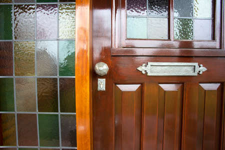 Front door with stained glass and metal door knob, vintage design close-up antique Archivio Fotografico