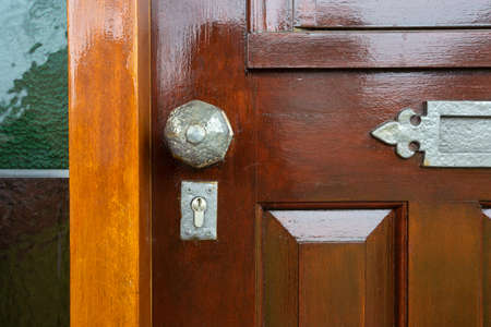 Front door with stained glass and metal door knob, vintage design close-up antique Stock Photo