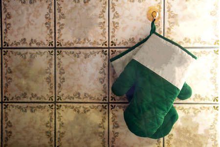 Green oven mitts hang on old-fashioned wall with pattern tiles antique design Foto de archivo