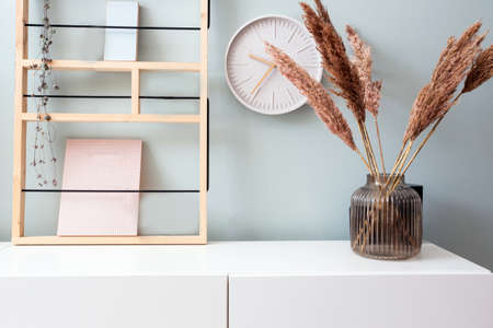 Retro modern decoration wall in the living room with pastel colors, white clock and shelf, modern vase with pampas grass scandinavian interior close-up Standard-Bild