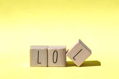 alphabet wood blocks forming the word lol on retro Yellow background, modern design