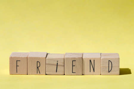 Friend word on wooden cubes with yellow background retro design Friend concept modern Imagens