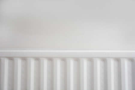 Close up of radiator against white wall modern new retro design. space for text