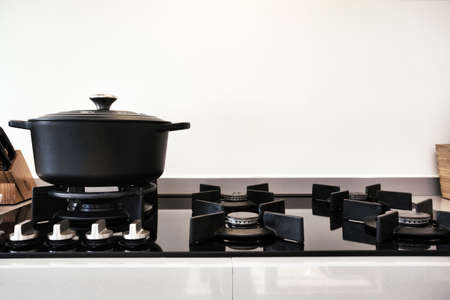 Cooking on a gas stove with a black modern iron casserole pan retro design close-up