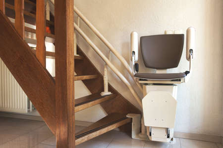 Automatic stairlift on staircase for elderly or disability in a house, taking people up and down