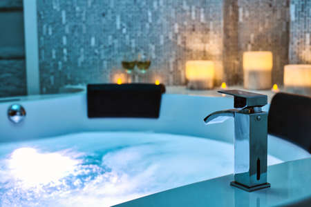 Blue bubbling Water in Spa close-up faucet decorated with candles on the background, Relax and Lifestyle Abstract Background with blue lights
