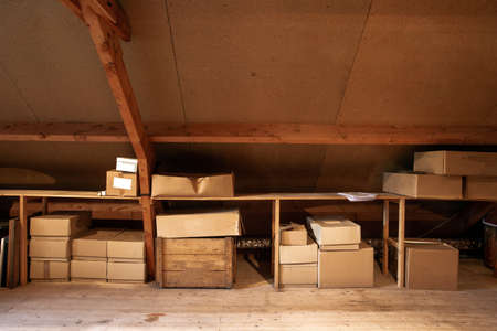 Old wooden attic interior with old cardboard boxes for storage or moving,
