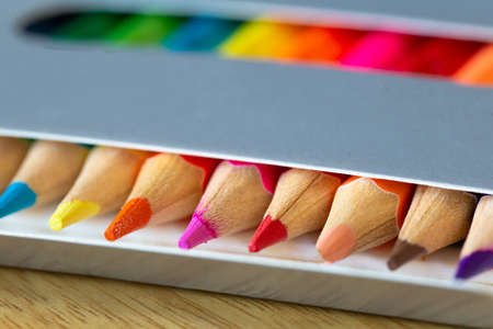 Colored pencils in a carton grey box, rainbow colors, orange pencil sticks out macro, school or office supplies background 免版税图像