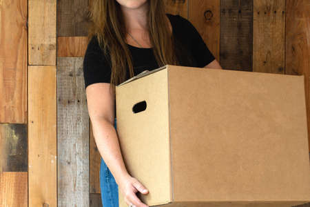 Happy young woman carrying a cardboard moving box for her new home, moving or new house concept