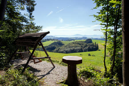 scenic mountain landscape shot with wooden swing sofa for looking at view, beautiful nature in the Alps