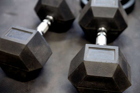 Dumbbells or weights on black rubber flooring tiles inside gym Concept for workout