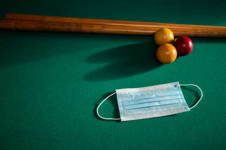 Blue medical face mask for Coronavirus on a green billiard table, protective medical mask for Covid-19 on pool,snooker table