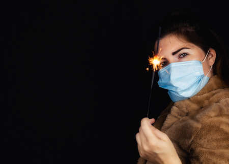 Happy new year, portrait of a young woman wearing medical mask and holding sparklers light in the dark for Covid-19, Coronavirus and New year concept Stock Photo