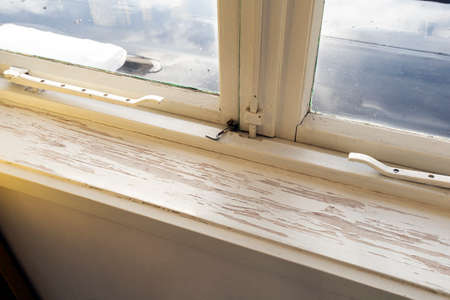 Old wooden window sill with cracked peeling paint and durt, needs renovation and repaired, replaced