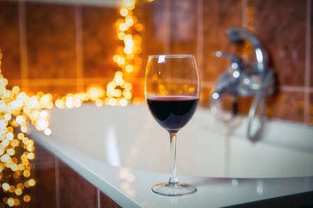 Close up of wine glass with red wine near bathtub with lights on the background, relaxtion and spa concept