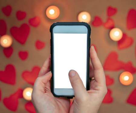 Female hand holding mobile phone taking a photo of Valentines background with romantic red hearts and candles. copy space, blank smarthphone