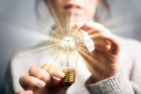 Female hand holding a shining light bulb, Great idea, innovation and inspiration, business concept background