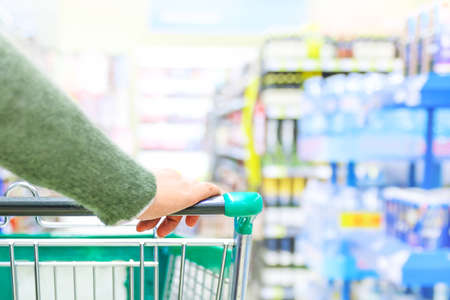 Close up of women hand pushing shopping trolley in supermarket, focus on hand Stockfoto