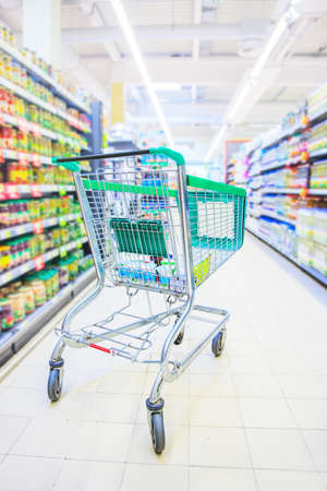 Shopping trolley with some groceries in supermarket