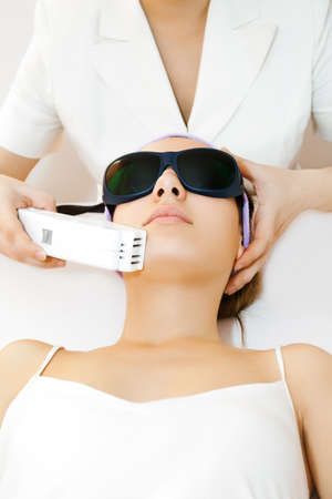 Young woman receiving laser epilation treatment Imagens