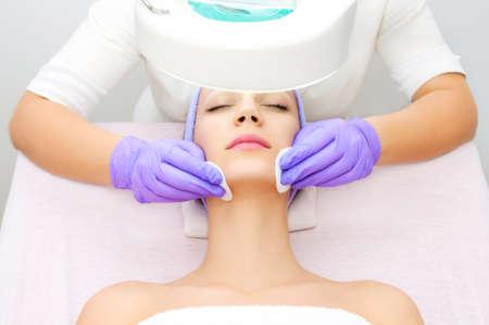 tratamientos faciales: Mujer joven que recibe terapia de belleza Foto de archivo