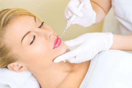 Jonge vrouw die botox injectie in de lippen
