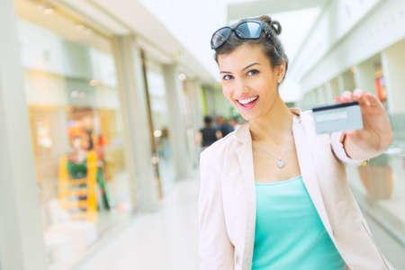 Het winkelen tijd, vrouw bij winkelcentrum met credit card