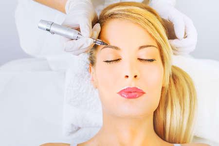 美人: 美容師の永久的な適用が眉をメイクアップします。