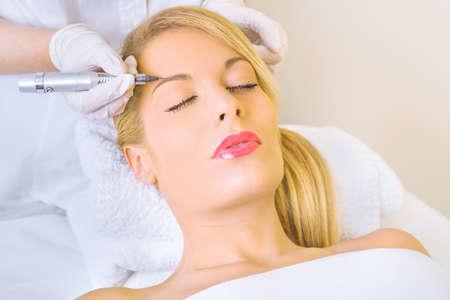 Cosmetologo applicando Trucco Permanente sulle sopracciglia