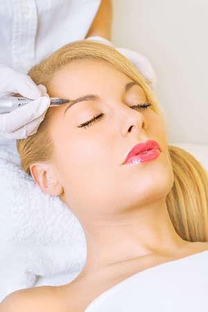 Cosmetologist applying permanent make up on eyebrows Stock Photo