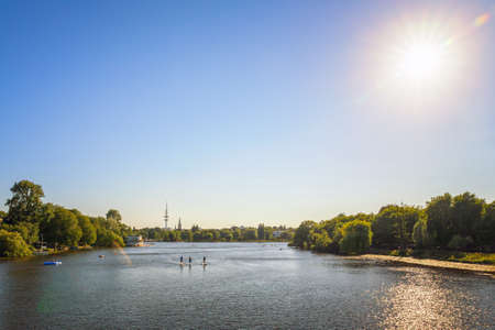 Alster Lake in Hamburg with people on a stand up paddle boards, with tv tower in the background